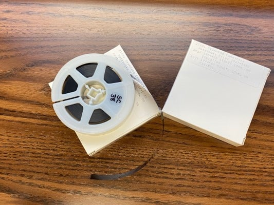 Reel of microfilm sitting on top of its container