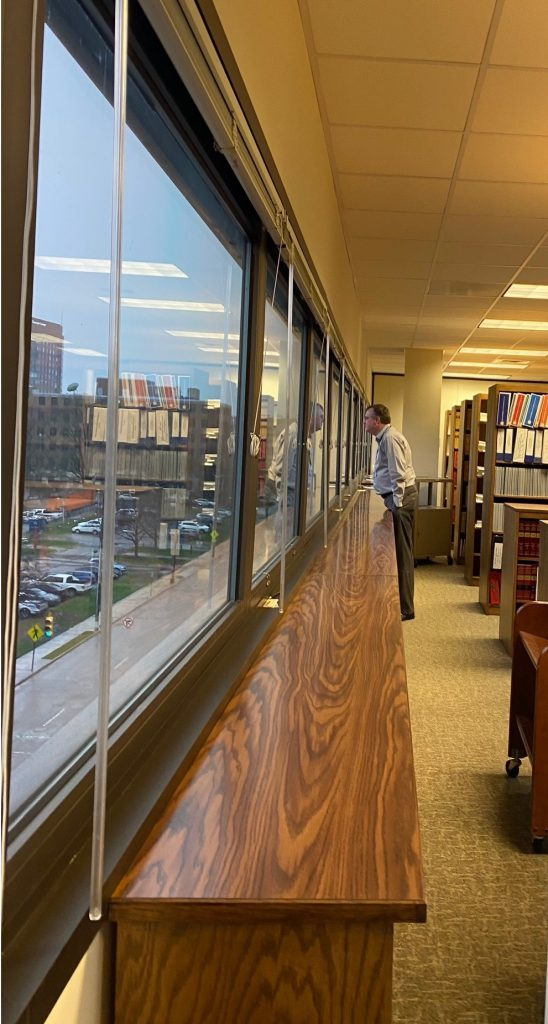 Librarian Anthony Aycock standing and looking out the Library window